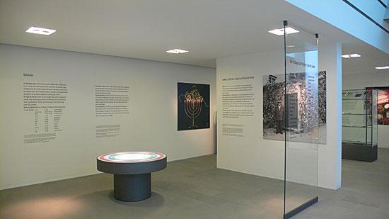 Beleuchteter Kalendertisch und Wandtexte im Untergeschoß